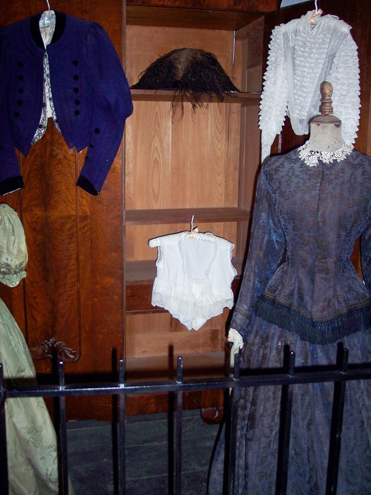 Interior of Sanchez Adobe in Woodside with period clothing and furniture from 1800s
