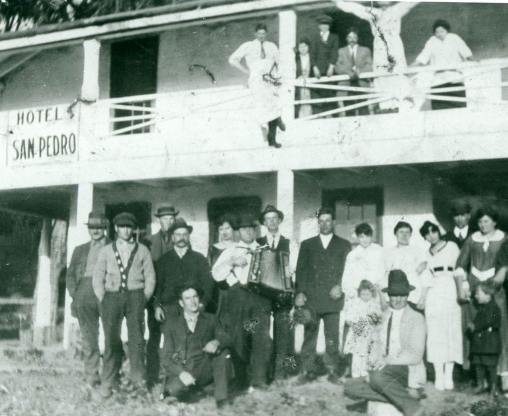 Archival photo of a group of people posing in front of Hotel San Pedro current site of Sanchez Adobe