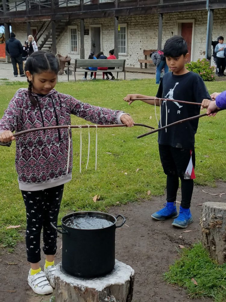 Students making traditional candles at Sanchez Adobe school program