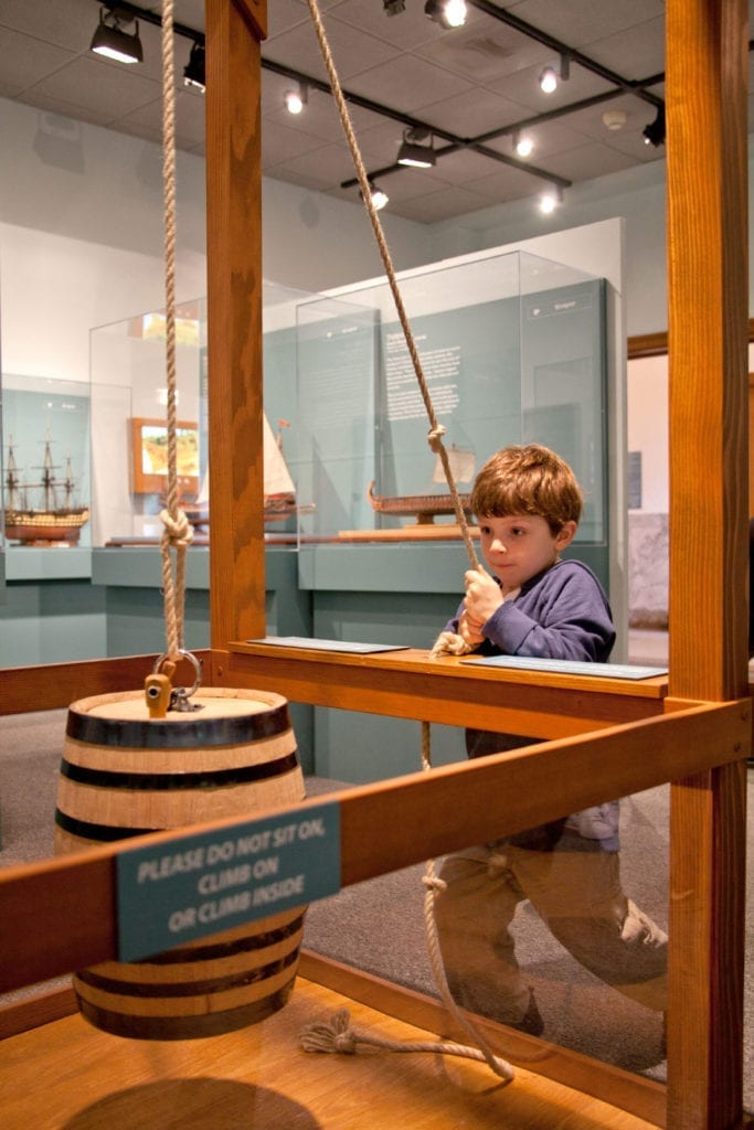 A young boy playing with an interactive display at Ships of the World exhibit at the San Mateo County History Museum