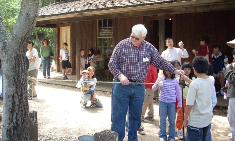 A docent with kids making twine at Rancho Fiesta Day