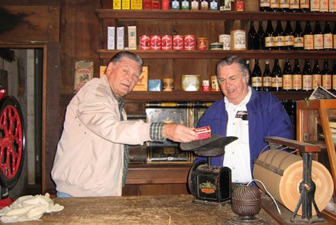 Two volunteers at the Woodside Store weighing a box on an antique scale