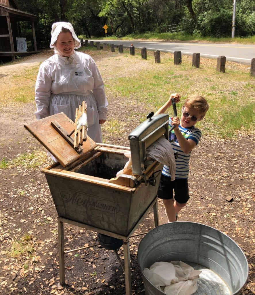 A young boy washes laundry in an antique washing machine at Rancho Fiesta Day