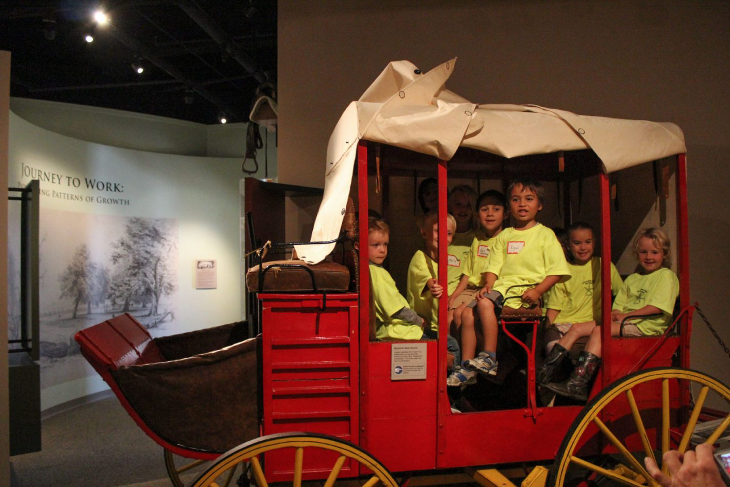 Young students seated in a wagon at the Getting from Here to There school program at the San Mateo County History Museum