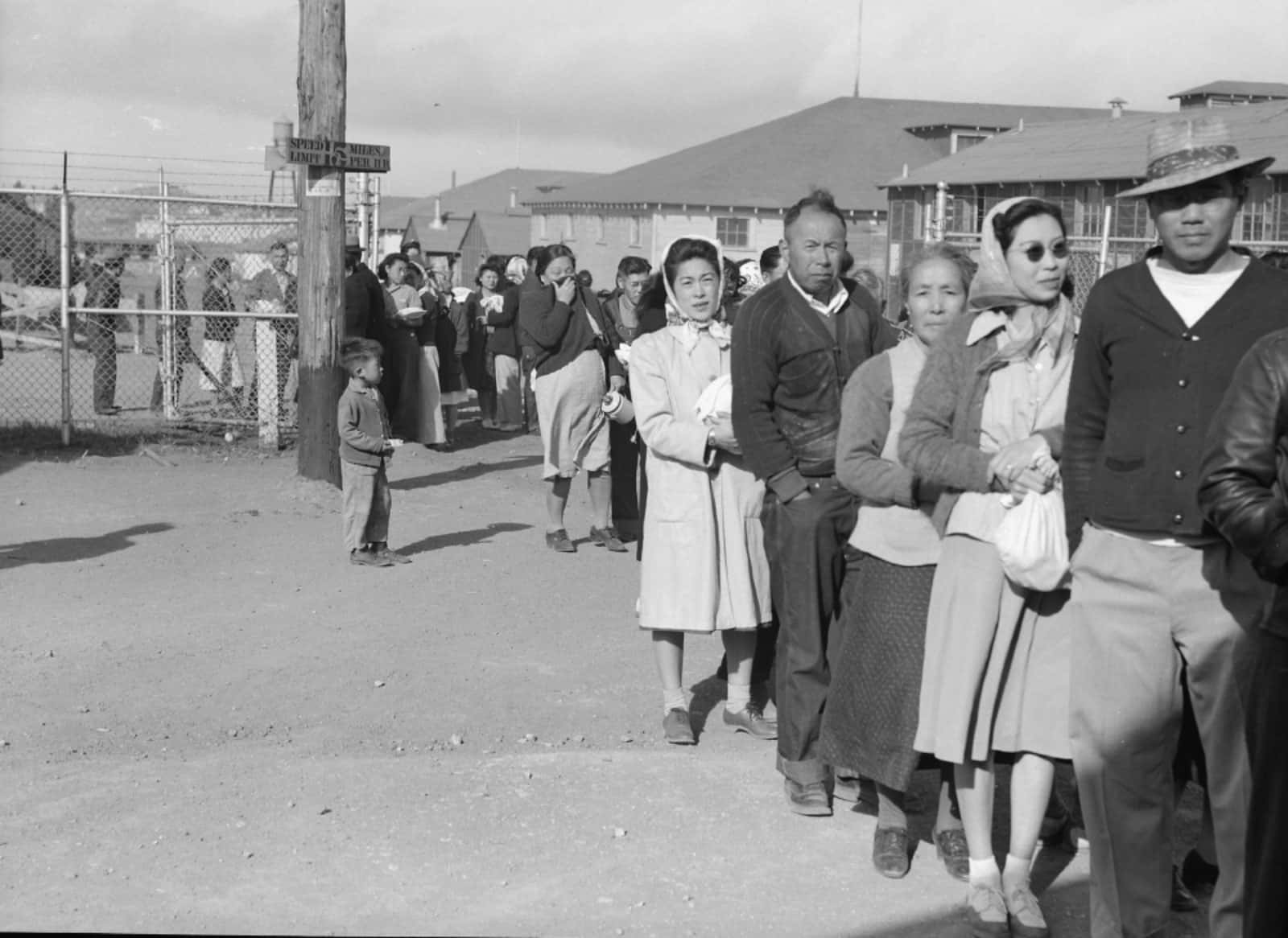 Archival photo of Japanese internment camp waiting in line for a meal