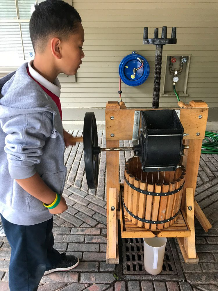 A student at the Folger Stable school program makes apple juice in an old fashioned press