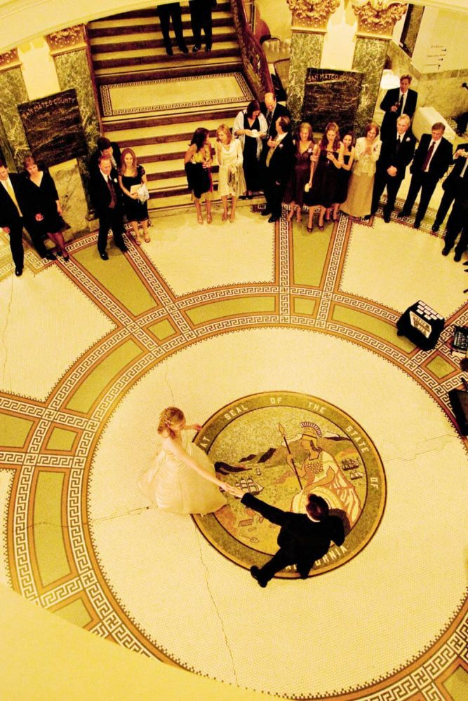 A bride and groom dance in the rotunda of the San Mateo County History Museum