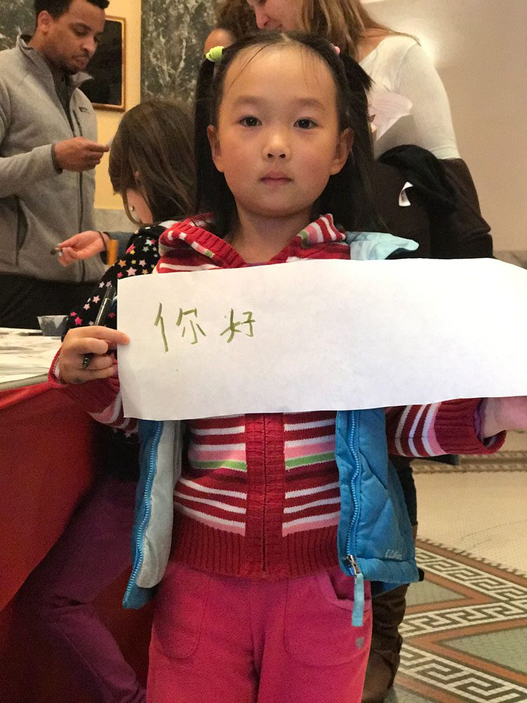 A young girl holds up chinese calligraphy at Lunar New Year celebration at the San Mateo County History Museum