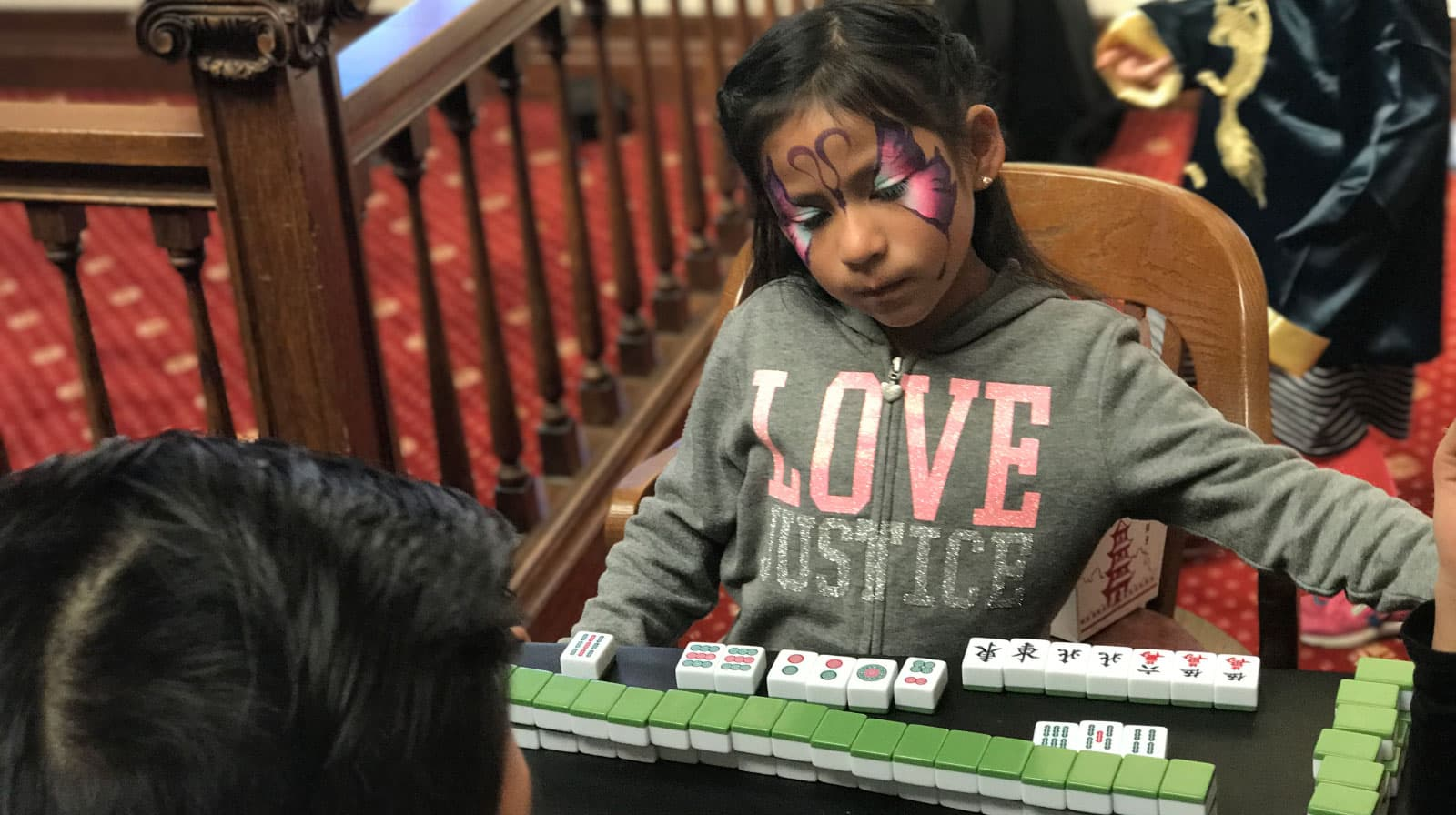 A young girl with butterfly face paint learns mahjong at the lunar new year celebration at the San Mateo County History Museum