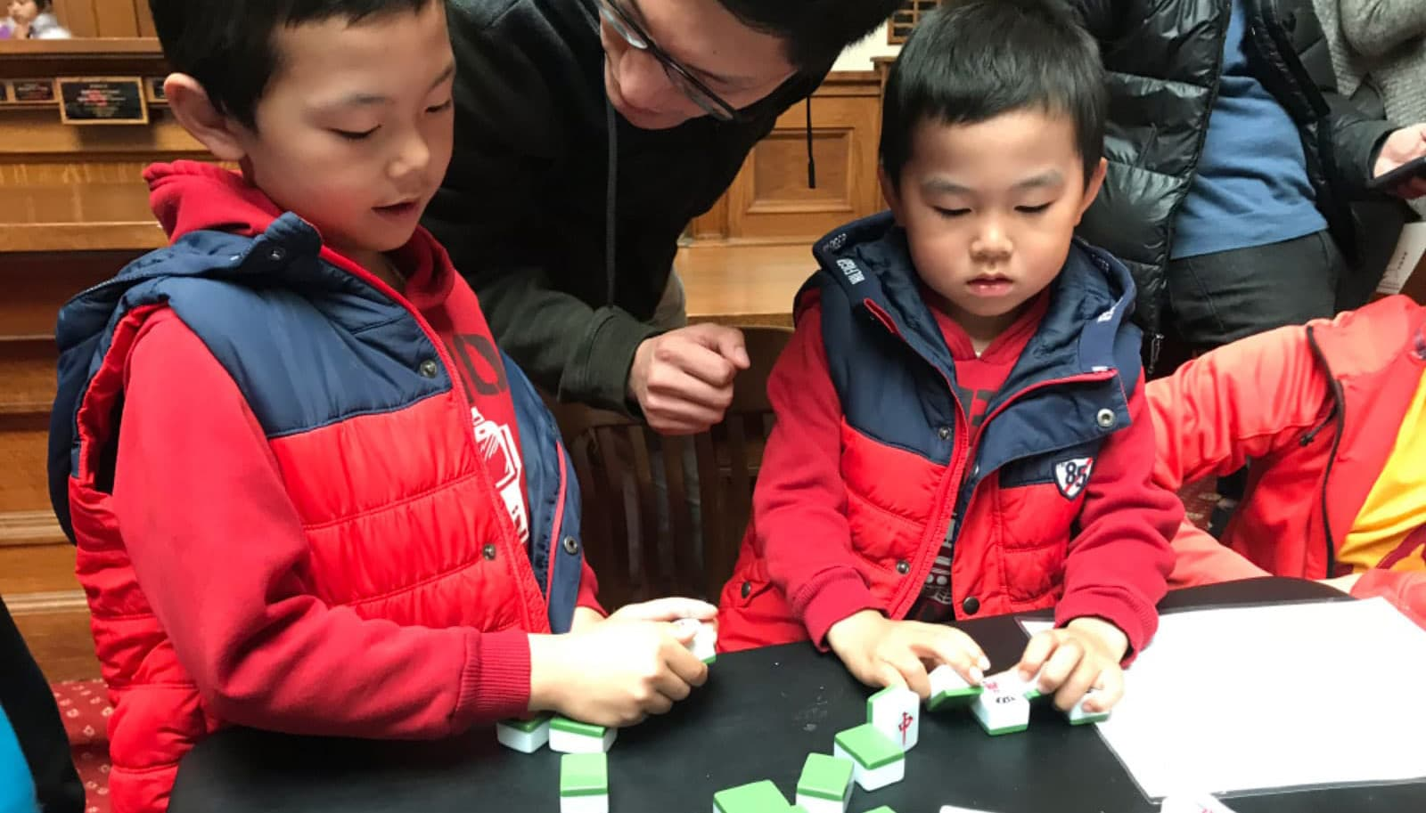 Two young boys learn mahjong at the lunar new year celebration at the San Mateo County History Museum