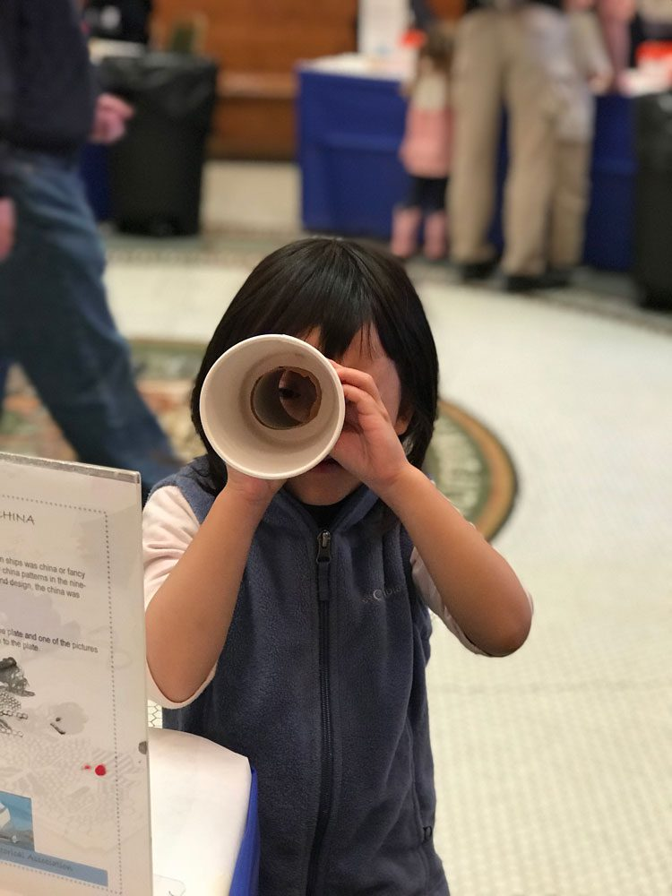 A young girl looks through a makes a handmade telescope craft at Maritime Day at the San Mateo History Museum