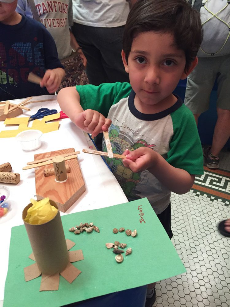 A young boy makes a boat craft at Maritime Day at the San Mateo History Museum