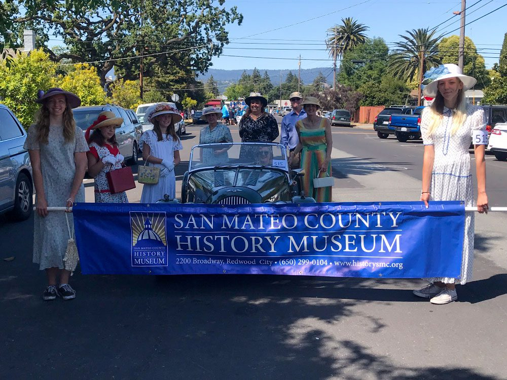Parade gatherers in period clothing and a vintage care holding a sign for the San Mateo County History Museum