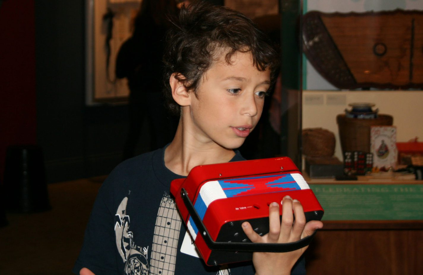 A young student plays a toy accordion at the People from Many Places exhibit at the San Mateo County History Museum