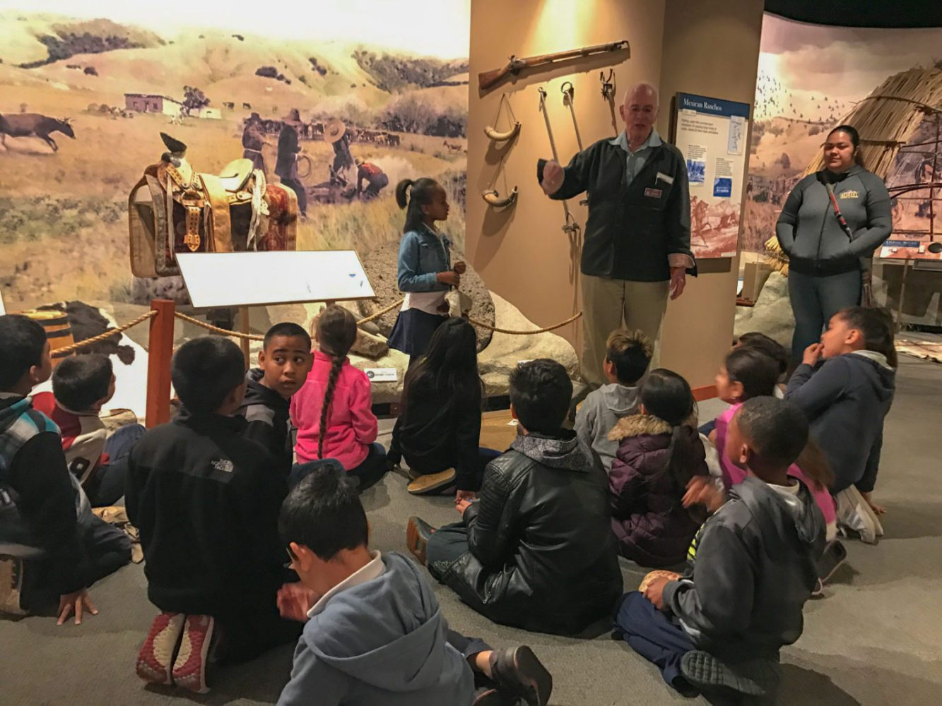 Students listen to a staff member at Providing Plenty school program at the San Mateo County History Museum