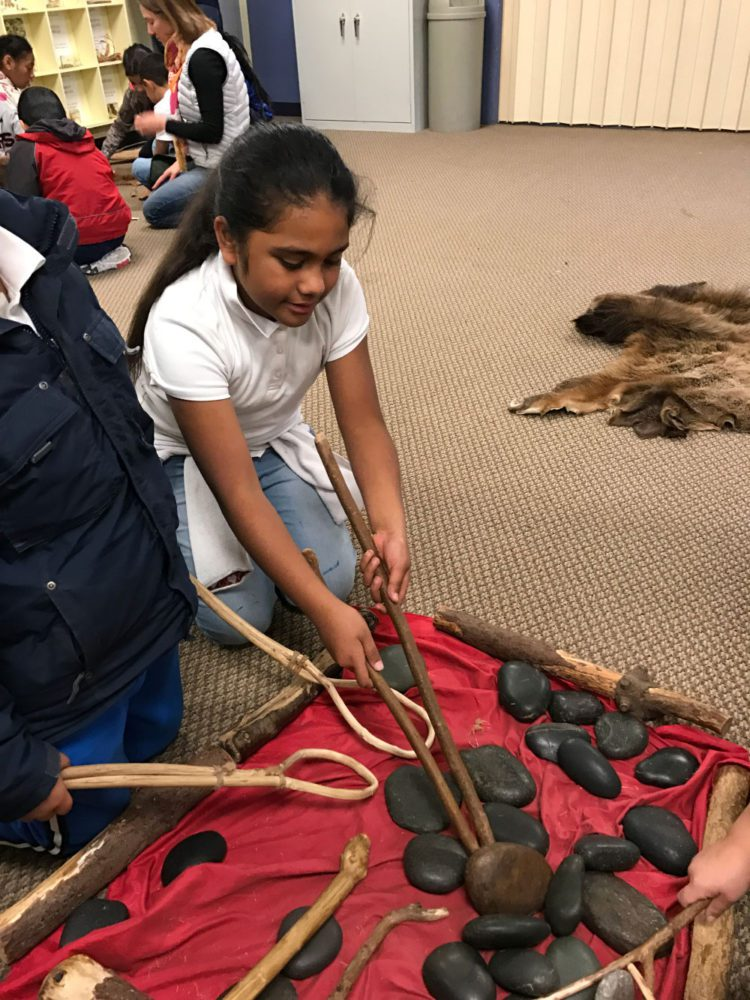 Young girl uses two sticks to pick up a stone at Providing Plenty school program at the San Mateo County History Museum