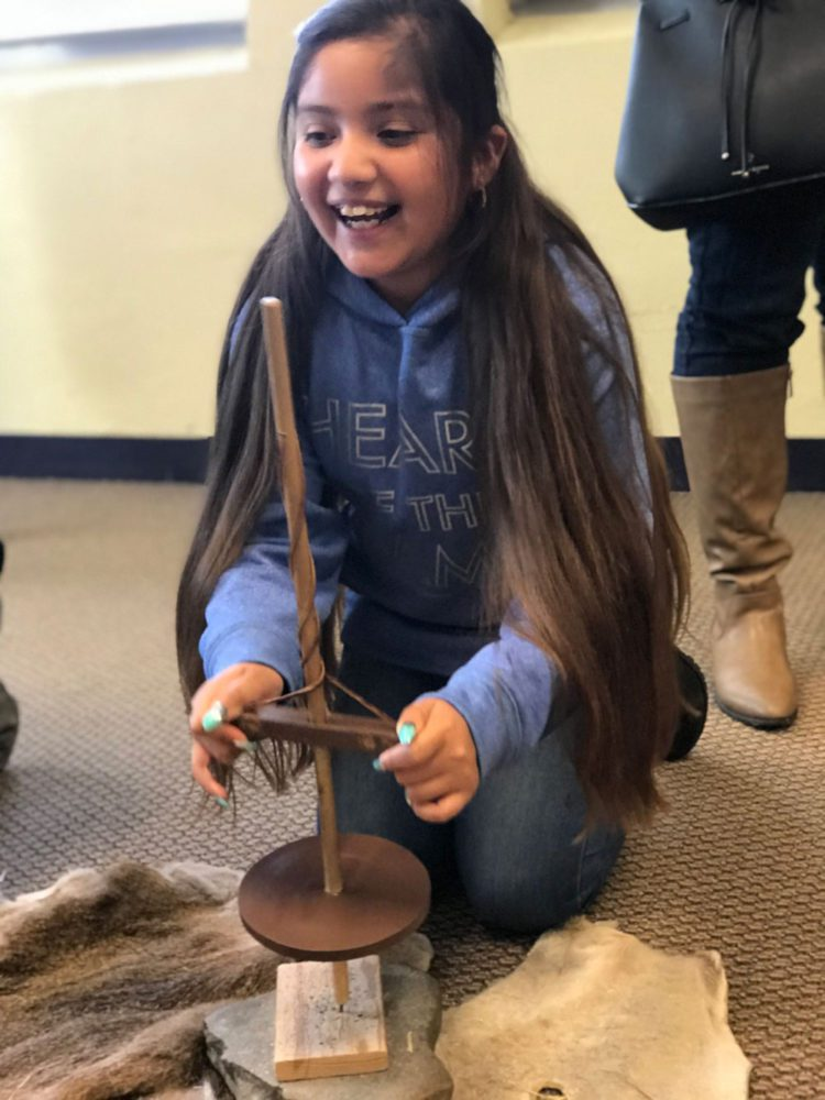 Young girl with a pump drill at Providing Plenty school program at the San Mateo County History Museum