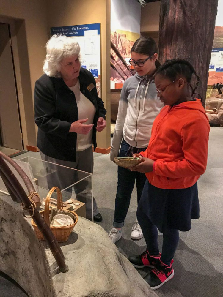 Students view a display with a staff member at Providing Plenty school program at the San Mateo County History Museum
