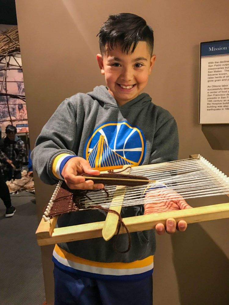 A young student plays with a loom at Providing Plenty school program at the San Mateo County History Museum