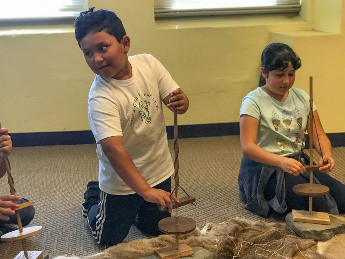 Young boy with a pump drill at Providing Plenty school program at the San Mateo County History Museum