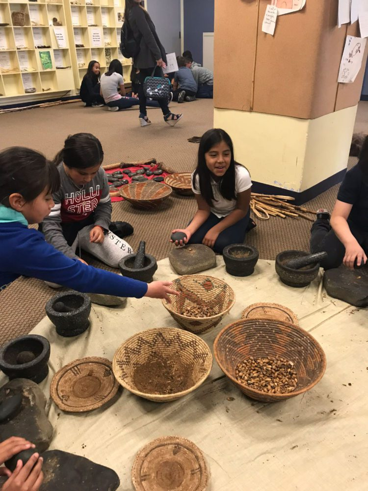 Students use a mortar to ground acorns at Providing Plenty school program at the San Mateo County History Museum