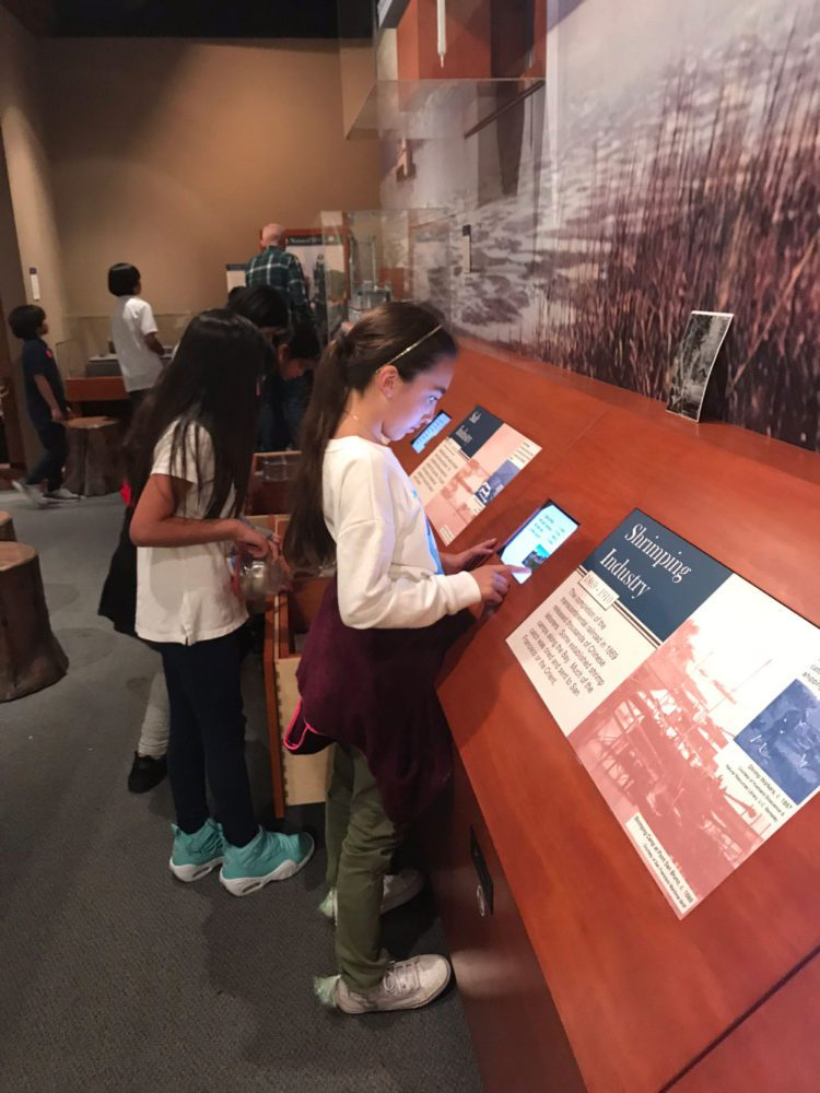 Young girl explores an interactive display at Providing Plenty school program at the San Mateo County History Museum