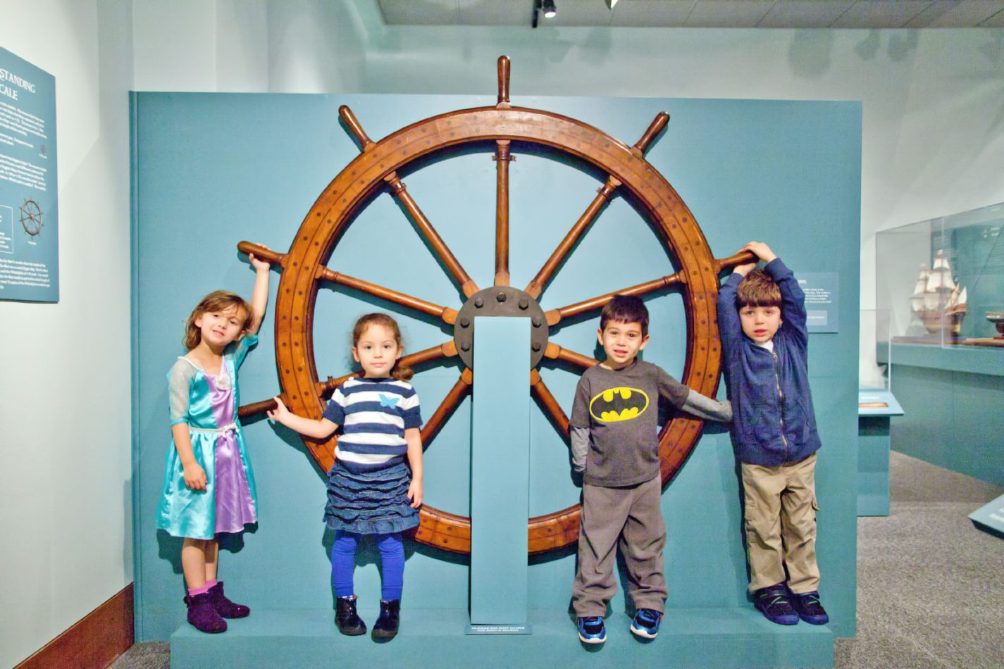 Children posing in front of a large ship steering wheel at Ships of the World exhibit at the San Mateo County History Museum