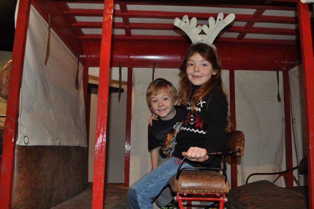 A young girl with festive antlers and young boy sitting in a carriage at Tree Treasures at the San Mateo County History Museum