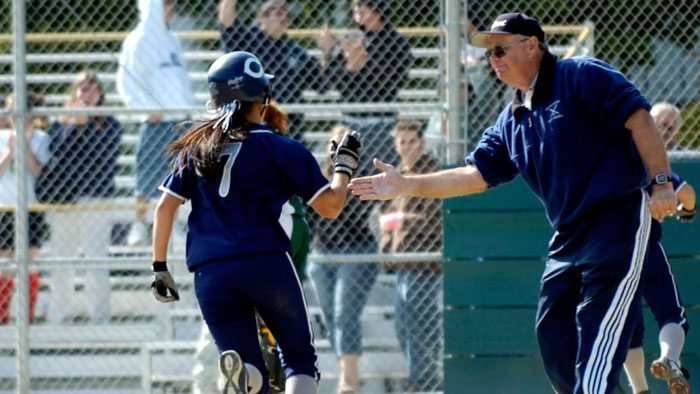 Girls softball coach Jim Liggit congratulates a softball player as she crosses home plate