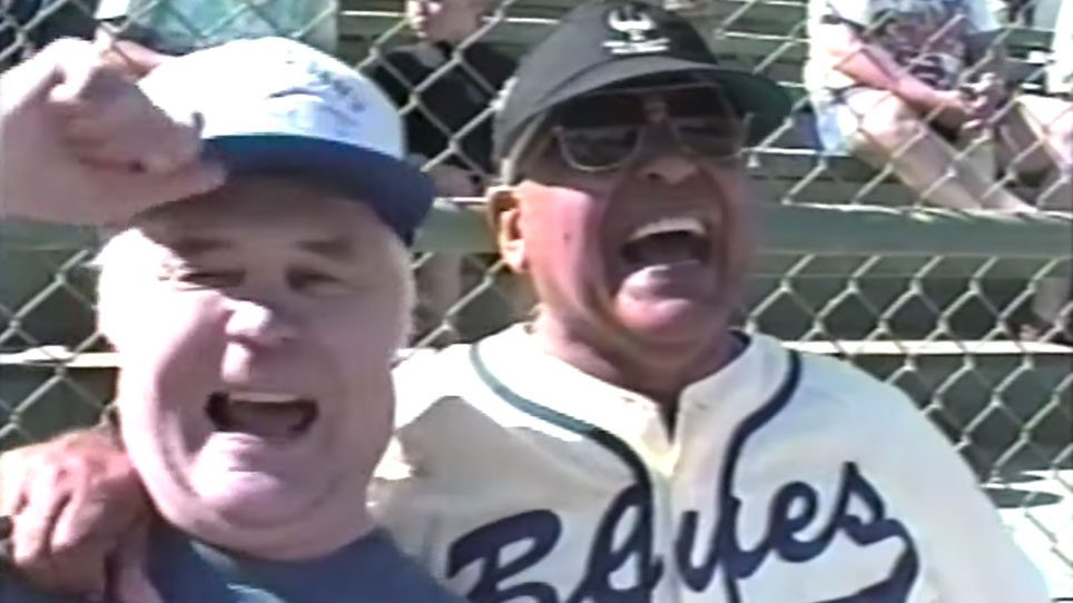 Two older men in baseball uniforms share a laugh at the Old Timers game