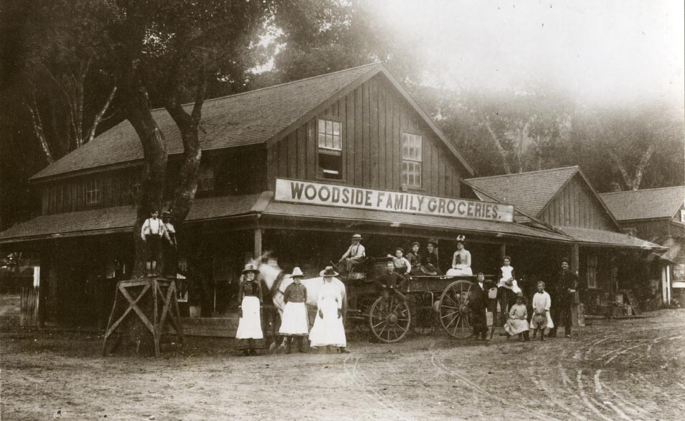 Archival photo of Woodside Family Groceries with family posing in front on horse drawn wagon 1854