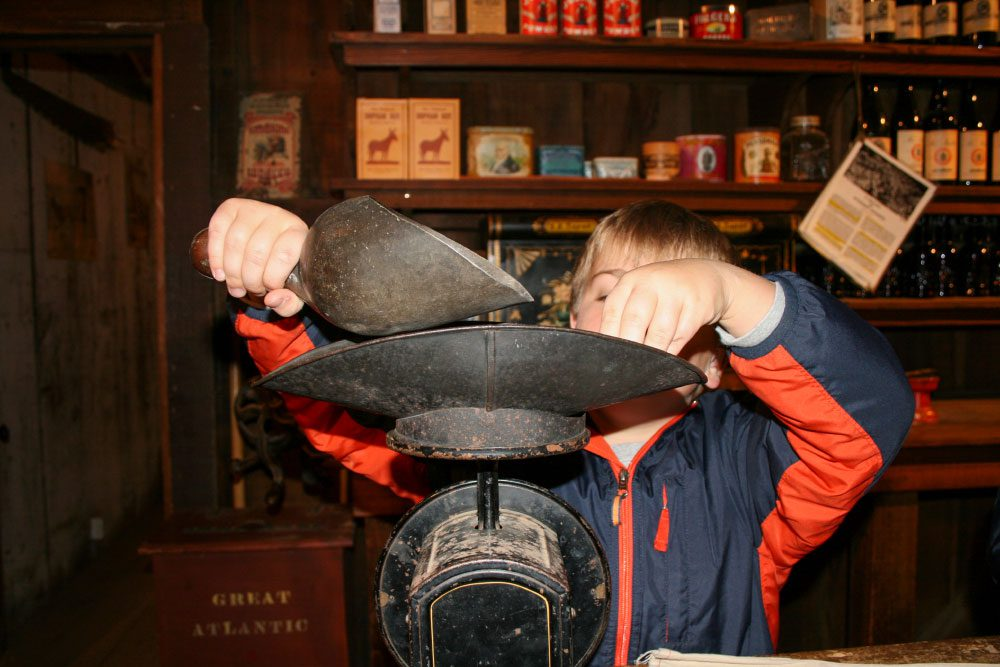 Young boy weighs items on an antique scale at Woodside Store School program