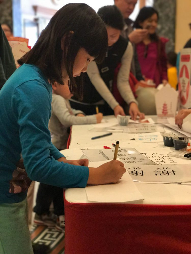 A young girl writes chinese calligraphy at Lunar New Year celebration at the San Mateo County History Museum