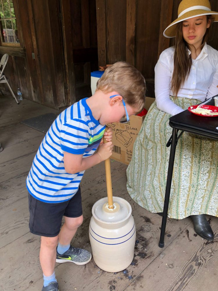 A young boy churns butter at the Old Woodside Store Day