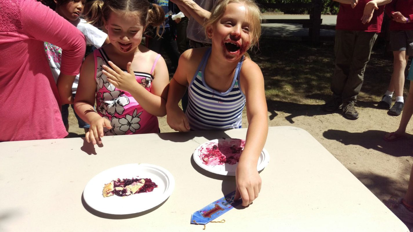 Two young girls eat pie at the Old Woodside Store Day