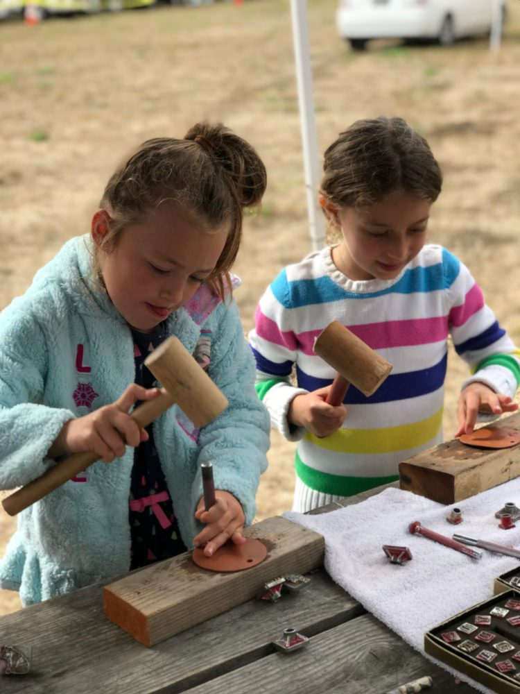 Two young girls work on a craft at Rancho Fiesta Day at Sanchez Adobe