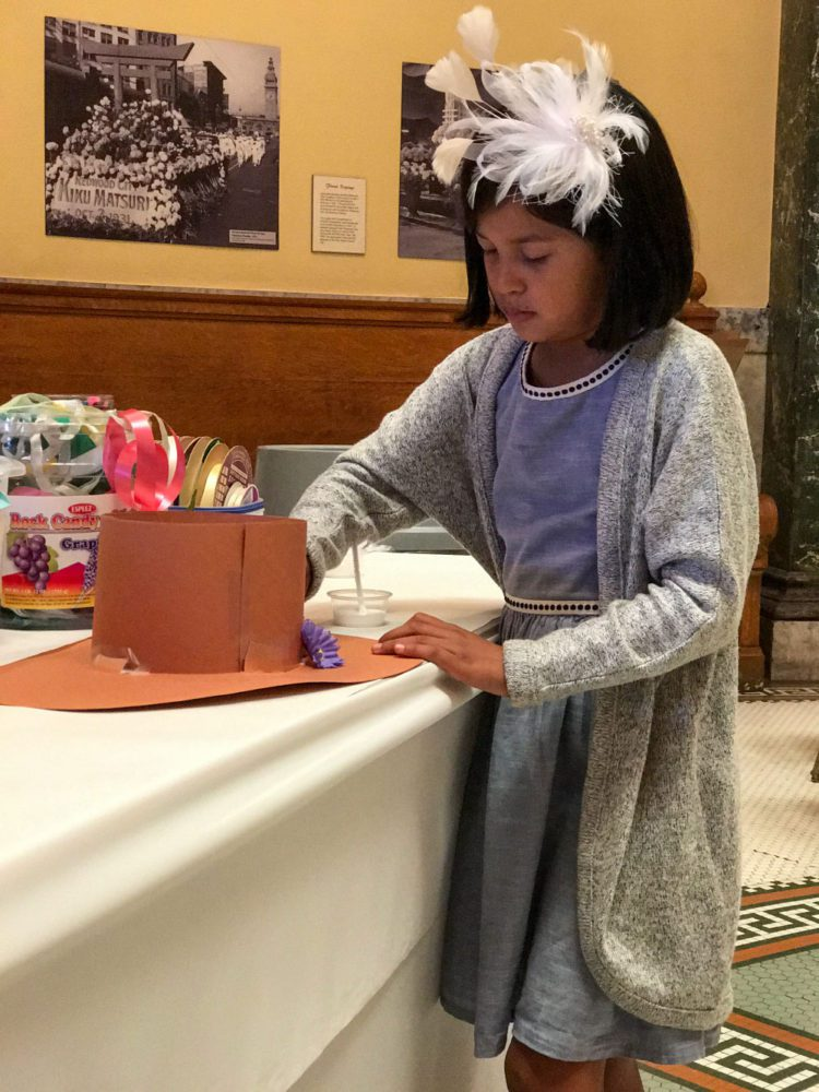 A girl makes a hat craft at Victorian Days at the San Mateo County History Museum
