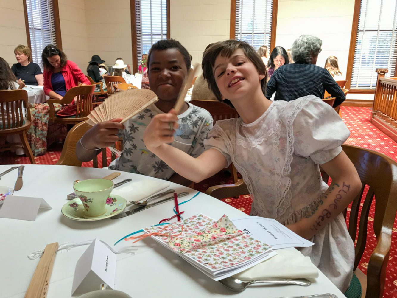 Two young visitors enjoy afternoon tea at Victorian Days at San Mateo County History Museum