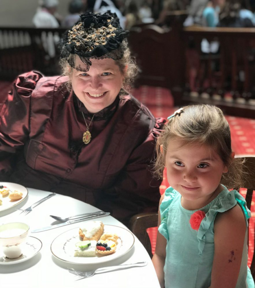A woman and young girl enjoy afternoon tea at Victorian dress at San Mateo County History Museum