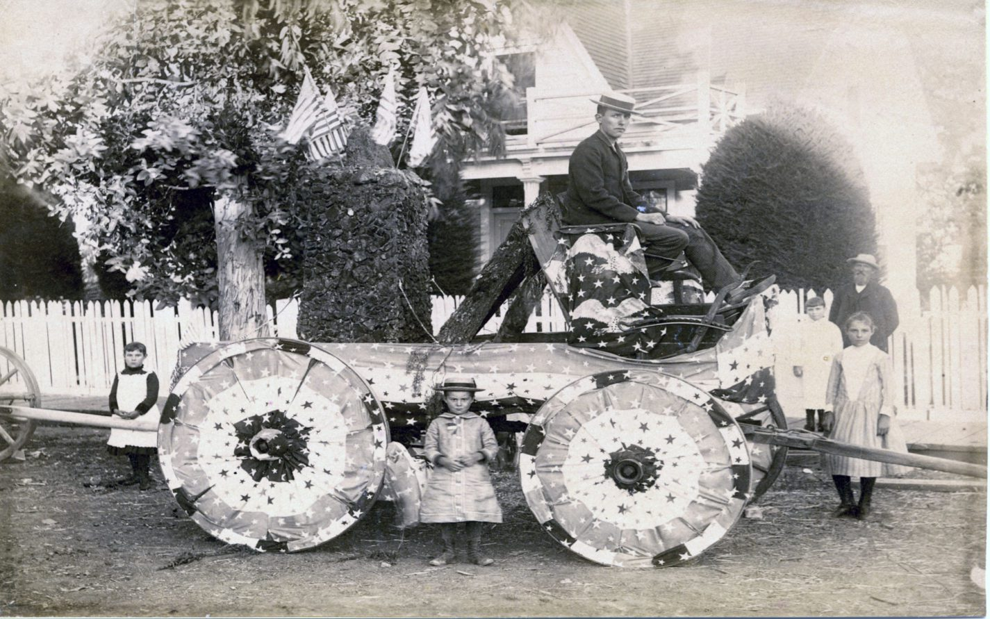 Family gathered around a Fourth of July float decorated with flags and flag bunting in front of a house circa 1880s