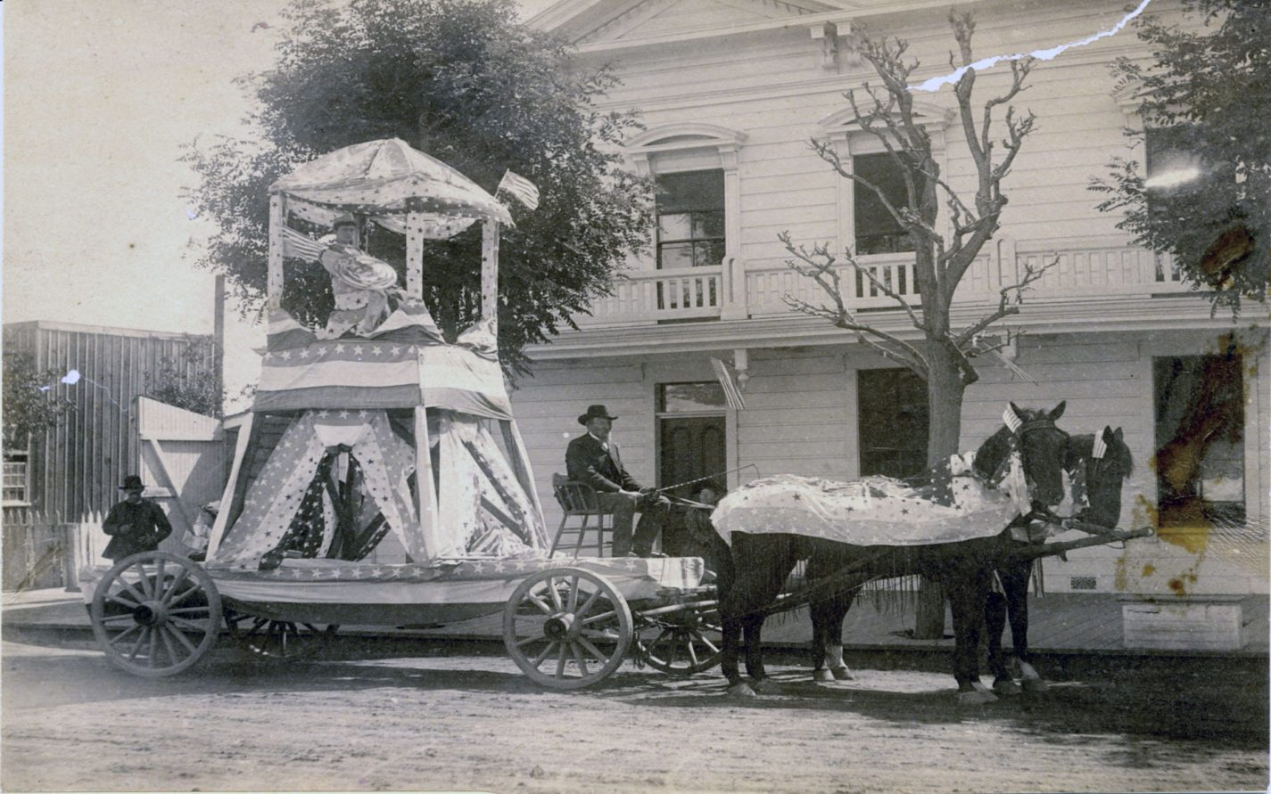 Young woman with a crown on July Fourth Float pulled by horses in front of the Tremont House on Main Street in Redwood City circa 1880s