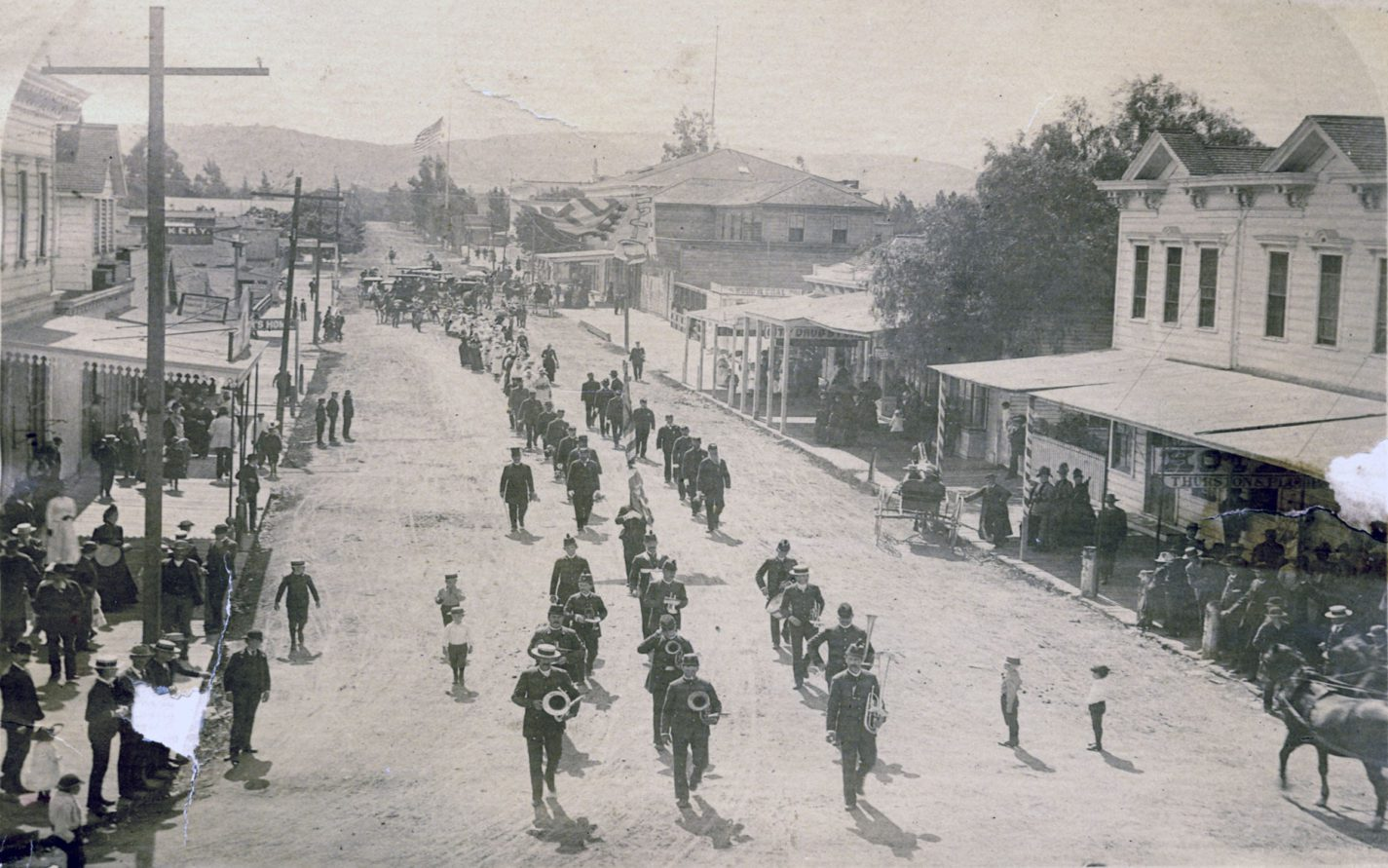 Band marches on Redwood City street during a Fourth of July parade circa 1880s