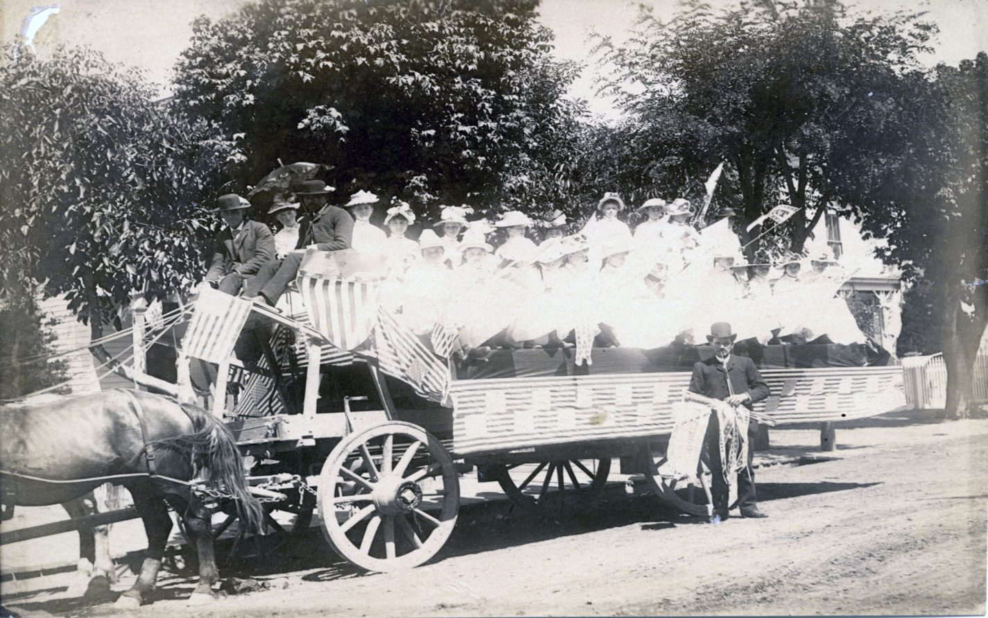 Float decorated with flags with a group of young girls dressed in white