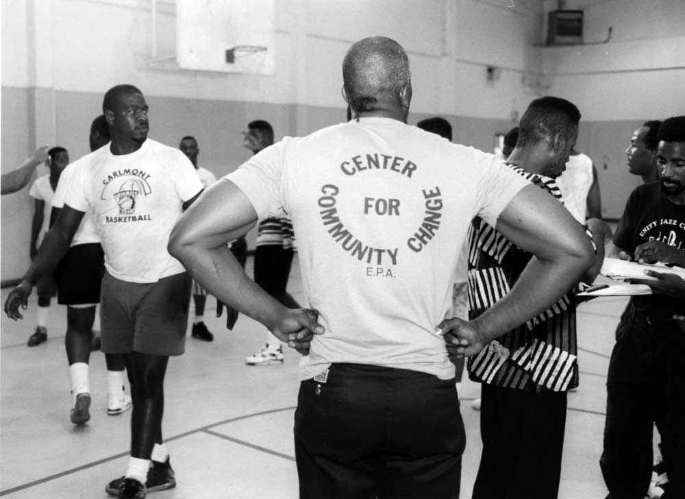 Midnight basketball try outs at Bell Street Gym with a man wearing a tshirt that says Center for Cummunity Change EPA