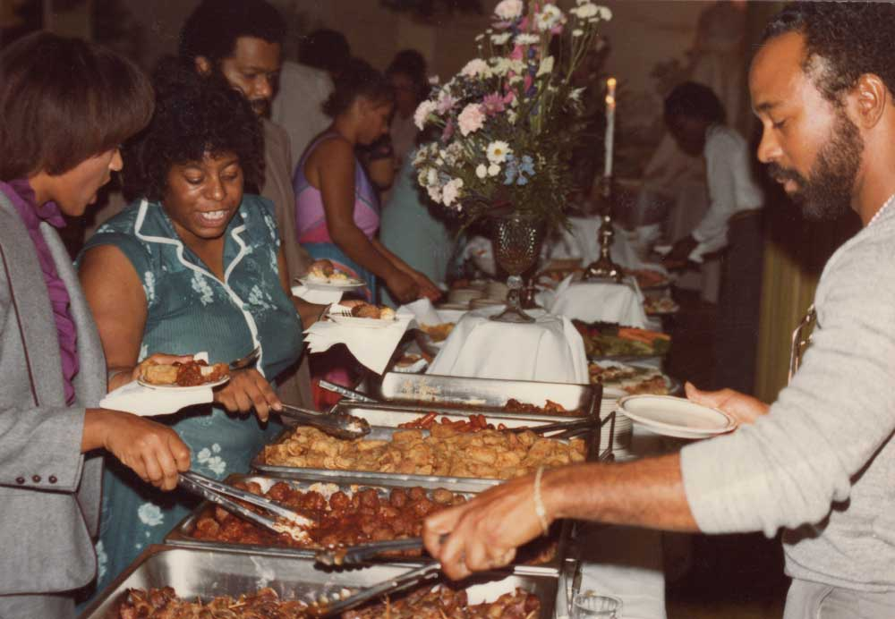 An African American community gathering potluck