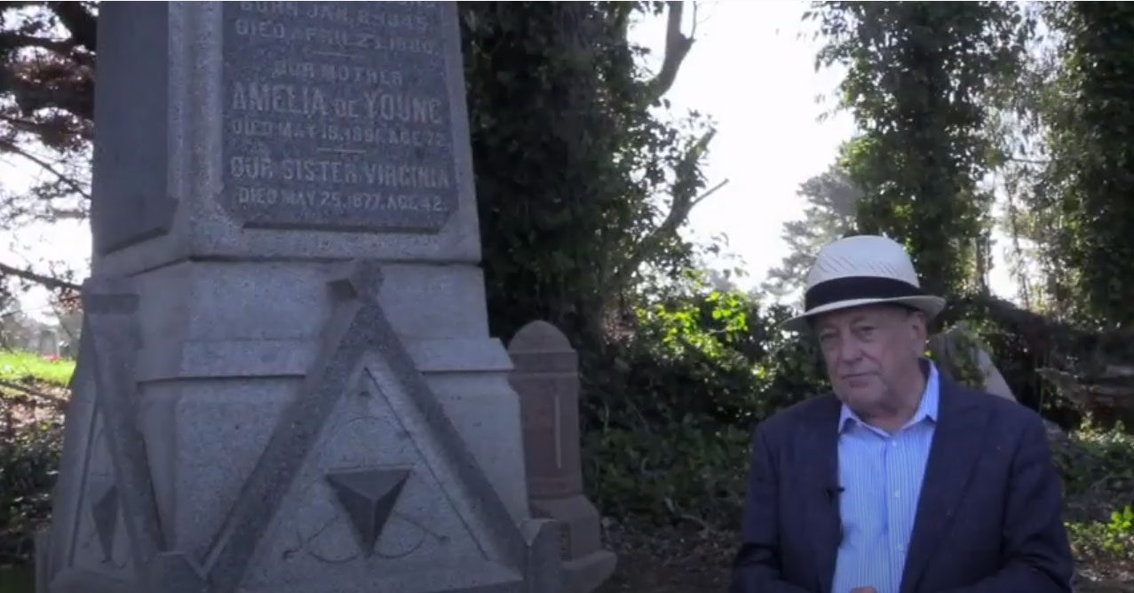 Man in front of large stone grave monument