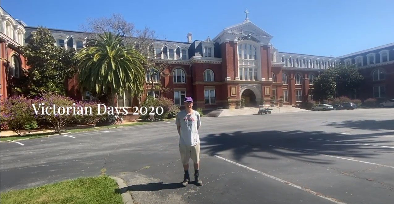 male tour guide in front of large brick building