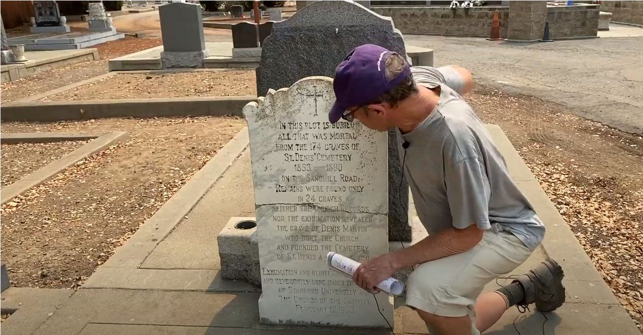 male docent kneeling in front of tombstone