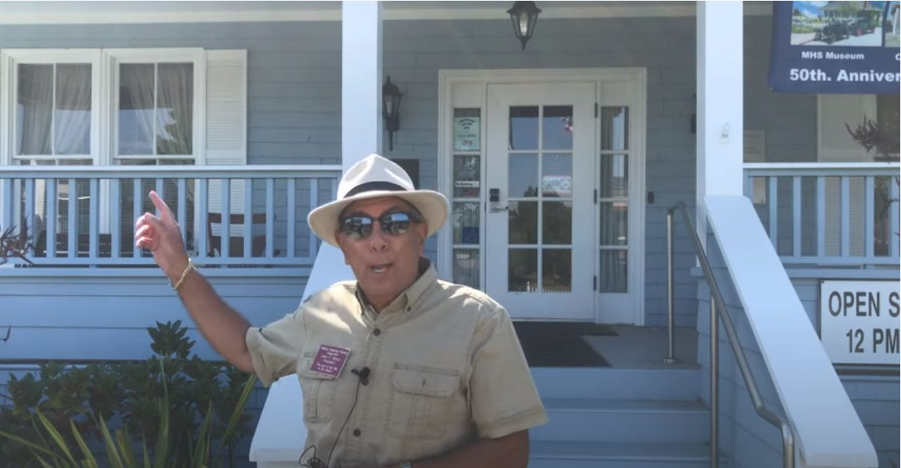 male docent in front of gray building with porch