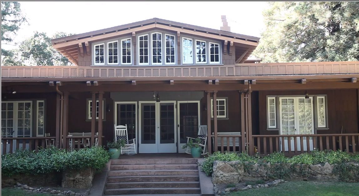 Brown house with many windows and large front porch